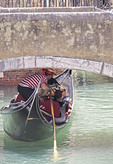 Godalier ducking to get under canal bridge in Venice.