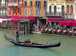 Gondola passing restaurants and hotels on the Grand Canal near Rialto Bridge in Venice.