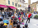 Street performers entertaining audience in Tuscan hilltop town of Montalcino.