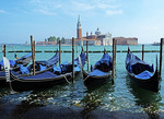 Gondolas along Venice lagoon with Church of San Giorgio Maggiore in background.
