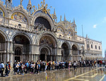 Tourists wading through flooded St. Mark's Square in Venice.