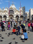 Tourists feeding pigeons in Saint Mark's Square (Piazza San Marco) in Venice (Veneza).