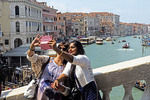 Women doing selfie photo on Rialto Bridge over Grand Canal in Venice.