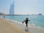 Tourist wading on Jumeirah Beach  with Burj al Arab Hotel in background.