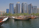 Dhows along Dubai Creek with high rise buildings in background.