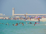 Jumeirah Beach in Dubai with Saturday crowd of swimmers and sun bathers.