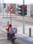 Motorcycle delivery man stopped at red traffic light in Abu Dhabi, UAE.