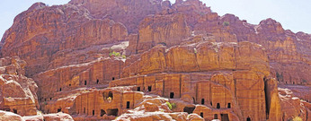 Panorama of facades sculpted into sandstone cliffs at Petra along Street of Facades.