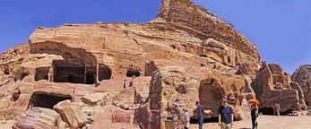 Panorama of facades sculpted into sandstone cliffs at Petra along Street of Facades.