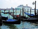 Costa cruise ship departing Venice lagoon past gondolas on waterfront.