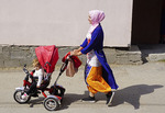 Woman strolling baby in Muslim village of       Woman strolling with child in Muslim village of Ribnovo, Bulgaria.