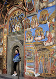 Chinese tourist posing with murals at Rila Monastery in Bulgaria.