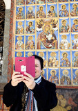 Woman taking selfie photograph with murals at Rila Monastery in Bulgaria.