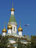 Plane landing in Sofia, Bulgaria, with Russian Church in foreground.