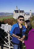 Couple taking a selfie photo at Mad King Ludwig's Neuschwanstein Castle in Bavaria, Germany.