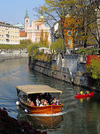 Ljubjlanica River in Old Town Ljubljana, Slovenia, with tourist cruise boat and recreational canoers.