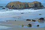 Bandon Beach walker at low tide by large sea stack rock formation.