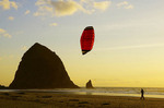 Kite flier at Cannon Beach with Haystack Rock sea stack in background.