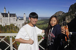 Young Chinese tourist couple doing a selfie at Neuschwanstein Castle in Bavaria, Germany.