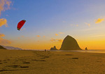 Kite flier on Cannon Beach with Haystack Rock at sunset on Oregon coast.