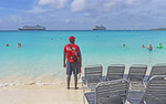 Lifeguard watching over cruise ship passengers enjoying beach at at Holland America's private Half Moon Cay in Bahamas with Zuiderdam and Veendam at anchor in distance.