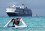 Snorkeler at Holland America Line's private Half Moon Lagoon Water Park in the Bahamas with Zuiderdam cruise ship in background.