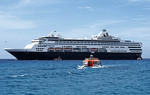 Holland America Line cruise ship Veendam with tender at anchor off Half Moon Cay in the Bahamas.