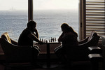Couple playing chess At The Crow's Nest on Holland America Line's Zuiderdam cruise ship near Aruba in Dutch Caribbean.