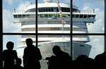 Cruise passengers waiting to board ship at Ft. Lauderdale's Port Everglades with Crystal Serenity seen through window.