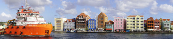 Panoramic of ship in channel along Willemstad waterfront of Caribbean island of Curacao.