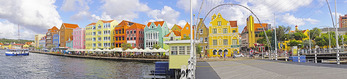 Panoramic view of colorful Dutch architecture on Willemstad waterfront with ferry and pedestrian swing bridge on Caribbean island of Curacao.
