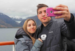 Young couple doing a selfie with cellphone camera from cruise ship with glacier on the Beagle Channel in Argentina.