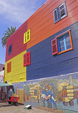 Colorfully painted building with mural of volunteer fire fighters in La Boca barrio of Buenos Aires, Argentina.