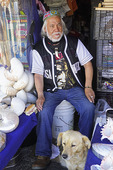 Elderly Chilean man with his pet selling seashells on the pier at San Antonio, Chile.