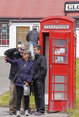 Trio doing a selfie with a red British telephone booth in Port Stanley, The Falkland Islands (Malvinas)>