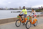 Couple riding along the waterfront on rented Orange Bikes in Montevideo, Uruguay.