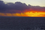 Rain squall blocking part of sunset in southern Atlantic Ocean.