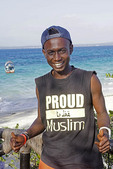 Young Muslim man on waterfront in Zanzibar.