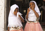 Two small Muslim sisters wearing hijabs in Zanzibar's Stone Town.