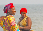Women from village waiting on fishing boats on shore of Lake Edward in Uganda's Queen Elizabeth National Park.