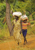 Rural Ugandan woman and young boy carrying sacks of produce on their heads in Crater Lakes district of Uganda,