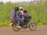 A boda-boda (motorcycle) carrying four near Kampala.