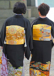 Japanese women wearing black and gold kimonos with gold obi in Fukuoka, Japan.