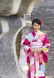 Young woman wearing rental kimono and holding kinchaku pouch at Kiyomizu Temple in Kyoto.