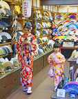 Young Japanese mother and daughter wearing kimonos in Kyoto shop selling fans.