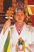 Shinto shrine maiden or miko wearing a traditional hakama kimono at Nara's Kasuga Taisha Shrine.