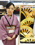 "Sales clerk wearing kimono in Tokyo department store with a ""Maru Obi"" or ""Fukuro Obi"" belt decorated with a gorgeous artistic design to be worn with a tradtional Japanese kimono."