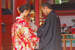 Bride and groom exchanging rings during wedding ceremony performed by Shinto priest in Nara's Grand Kasuga Taisha Shrine.