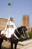 Royal guard on horseback at Mohammed V Mausoleum with Hassan Tower in Rabat, Morocco.