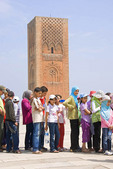 Students lined up to visit Tour Hassan, an unfinished Mosque with minaret in background, in Rabat, Morocco.